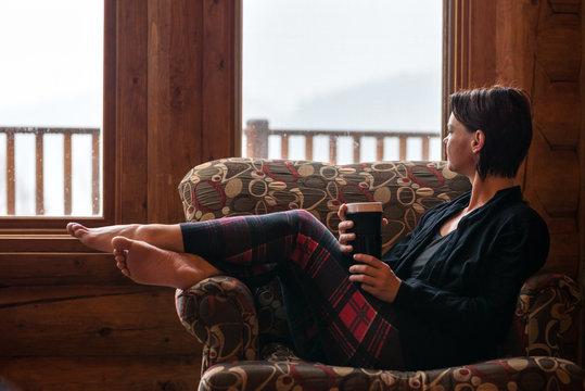 Woman Wearing Plaid Tights At Ski Chalet Enjoying Morning Coffee