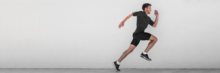 Running man runner training doing outdoor city run sprinting along wall background. Urban healthy active lifestyle. Male athlete doing sprint hiit high intensity interval training. Banner panorama.