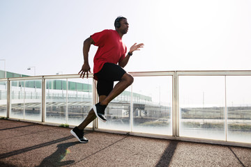 Young athlete running on a bridge.