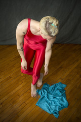 Young woman in red unitard looking at a blue scarf.