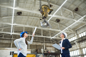 Side view portrait two female engineers wearing hardhats examining workshop of modern factory looking at big crane hook, copy space