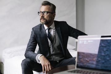 Stylish mature businessman with laptop