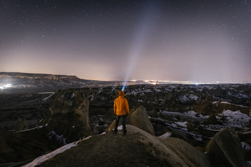 young male adventurer with headlamp overlooking snowcovered landscape of cappadocia at night, turkey