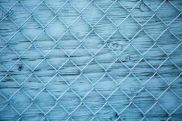 Blue wire mesh fence over blue wooden wall