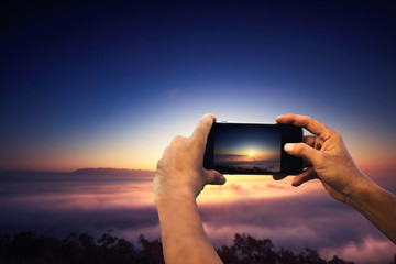 Closeup on traveller man taking photo with smart phone on mountain, amazing summer foggy landscape, mountains, beauty photo