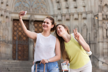 tourists walking in the town and taking selfie on phone