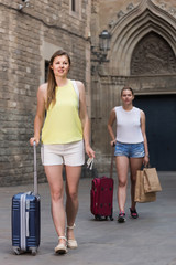 female tourists  exploring old european city with baggage