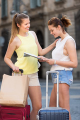 Two traveling females using paper map in town
