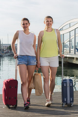 young women with luggage  posing on quay and smiling