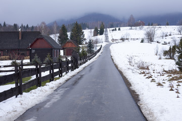 Road in Bieszczady to Wetlina and Solina, Winter day with lot of snow. Buildings in the background