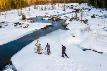 Two Men Snowshoeing Through the Woods on Winter Day
