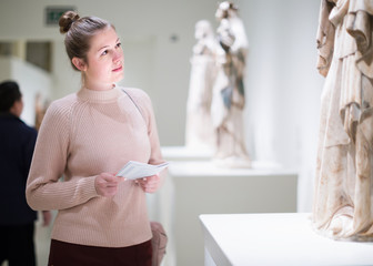 Woman with guidebook looking at  sculptures in museum