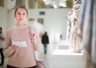 Portrait of female with guidebook looking at  sculptures