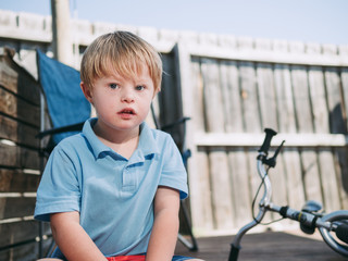 Blonde Boy in Backyard Looking at Camera