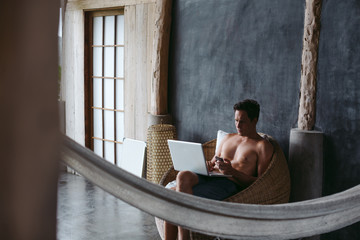 Man in his 30's working on laptop in chair on vacation