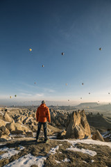 young male traveller overlooking snowcovered landscape of cappadocia with dozens of colorful hot air balloons at sunrise, turkey