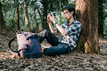 Asian man taking picture in forest
