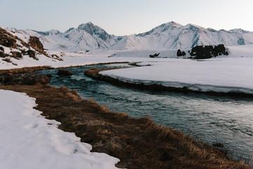 River flowing through a snowy mountainous landscape at dusk