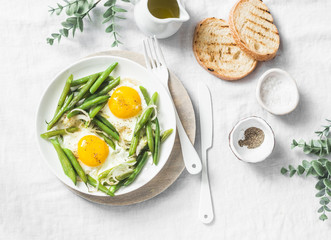 Healthy breakfast or snack - a fried egg with green beans on a light background, top view