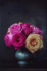 Overblown roses in a pewter jug