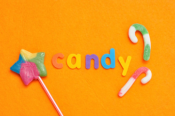 The word candy displayed with a star shape lollipop and candy canes