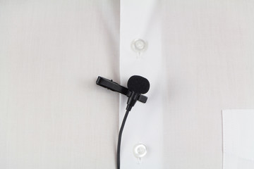 Lavalier microphone on white man's shirt