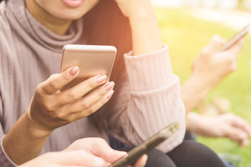 Asian teenager friends group using smart phone at a park having fun together ,sharing,social life,technology with people concept,selective focus