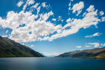 Simple Perspective background, only water, hills and puffy clouds in the sky, at Lake Wakatipu in the Southern Island of New Zealand.