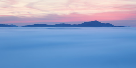 Fototapete - Dramatic clouds with mountain silhouette in dawn, Slovakia.