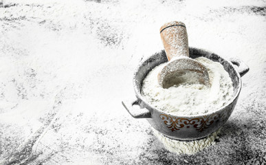 Flour with a scoop in a bowl.
