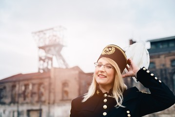 Woman in black coal miner foreman gala uniform with white feather on hat.