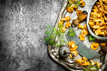 Fresh chanterelles mushrooms with herbs and an old knife on a steel tray.