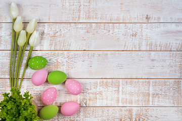 Colorful easter eggs and tulips over white wooden table