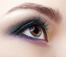 Closeup macro shot of human female eye. Girl with perfect skin and lilac - blue - yellow eyes shadows