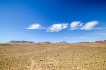Beautiful wide angle view of the Namibian Desert and mountains in the background at the road between Vioolsdrift and Aussenkehr near the South African border. Blue sky and beautiful clouds.