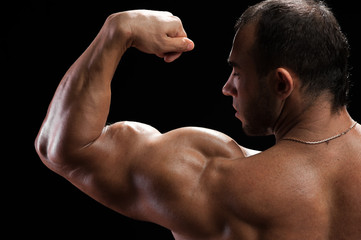 Closeup of handsome muscular bodybuilder showing biceps muscles