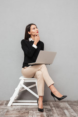 Full length image of Pensive smiling woman in business clothes