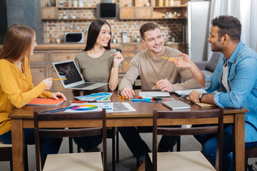 Sharing ideas. Enthusiastic positive creative woman sitting at the big table with a modern laptop in her hands and smiling while listening to her clever colleagues