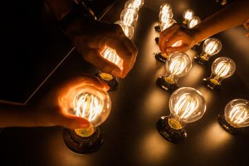 People touching light bulbs