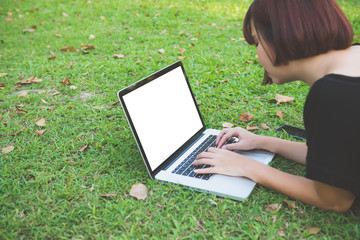 Mockup image of a woman using laptop with blank white screen lying on grass in nature outdoor park. Happy hipster young asian women working on laptop in park. Lifestyle and technology concepts.