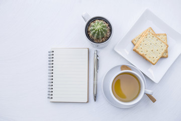 Blank notebook with hot tea and biscuit on white table background, tea break time