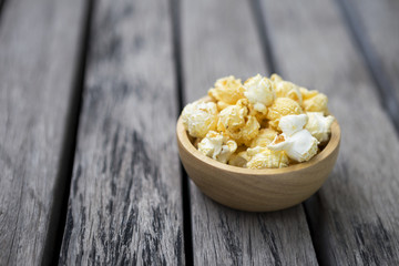 Salted popcorn in round wooden bowl on wooden table, snack for movie