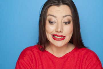 picture of woman  in a red blouse on a blue background with facial expression of mistake