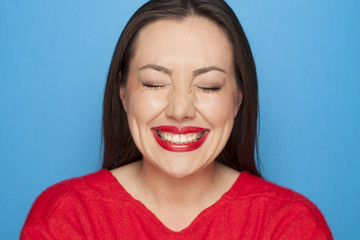 beautiful ashamed woman in a red blouse on a blue background