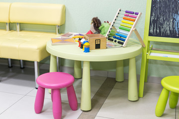 childhood, development, pedagogy concept. there is place for playing children equiped with small table and chairs and blackboard, on the table there is colorful abacus and some toys