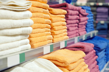 A set of multi-colored towels on a shelf in a store.