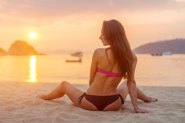Rear view of slim female model sitting on seashore wearing bikini looking away during sunrise with sun path reflected water