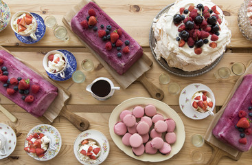 Overhead view of desert table with homemade pavlova summer pudding and macaron