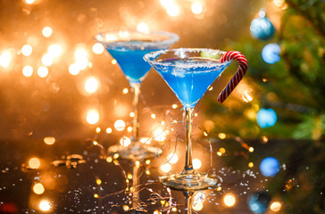 Christmas photo of two wine glasses with blue cocktail and garland
