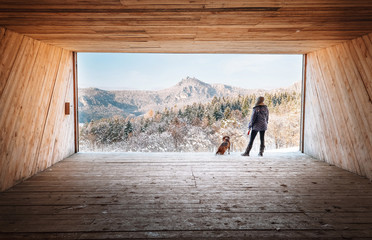 Woman with dog stay in big wooden hangar and looks on snowy mountains